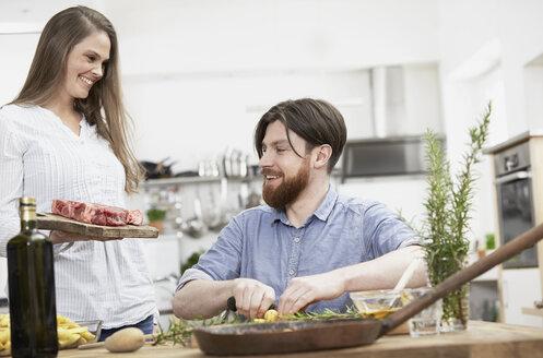 Happy couple preparing food in kitchen - FMKF000987
