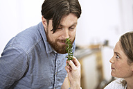 Man smelling at twig of rosemary - FMKF000990