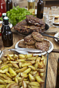 Dish with potatoes, steaks and meatballs on wooden table - FMKF001071