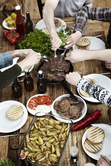 Friends eating potatoes, steaks and meatballs at wooden table - FMKF001074