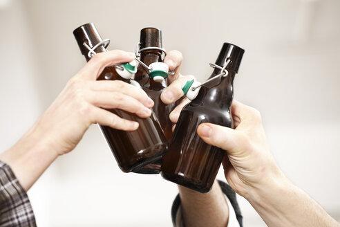 Friends clinking beer bottles - FMKF001019