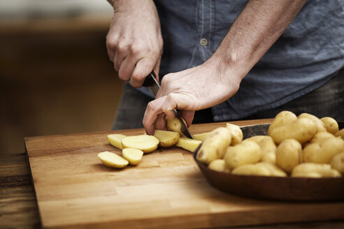 Man cutting potatoes in kitchen - FMKF001041