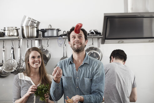 Man juggling with food in kitchen - FMKF001062
