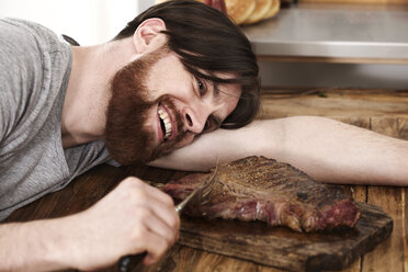 Happy man lying on table looking at large steak - FMKF001099
