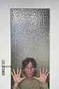 Man looking through ribbed glass pane of door - MUF001456