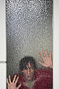 Man looking through ribbed glass pane of door - MUF001457