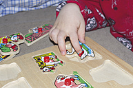 Hand of toddler playing with wooden puzzle - MU001439
