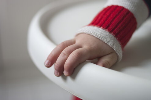 Hand of toddler holding edge of baby high chair - MUF001440