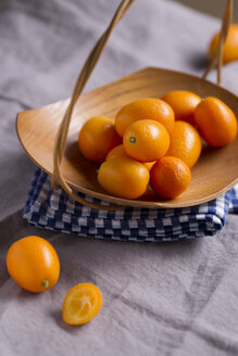 Wooden bowl of kumquats on kitchen towel and cloth - MYF000205