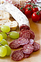 Chopped salami, green grapes, tomatoes and baguette on chopping board - SARF000292