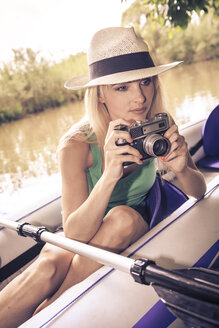 Blond woman with camera in a boat - VTF000125