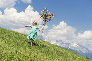 Austria, Salzburg State, Altenmarkt-Zauchensee, young girl with Palmbusch running down alpine meadow - HHF004769
