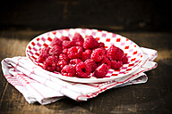 Dish of raspberries on kitchen towel and wooden table - MAEF008076