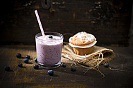 Glass of blueberry milkshake, blueberry muffin and blueberries on wooden table - MAEF008090