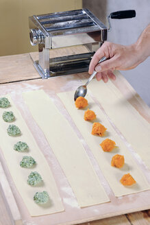 Spreading pumpkin filling on pasta dough for home-made tortelloni - IPF000086