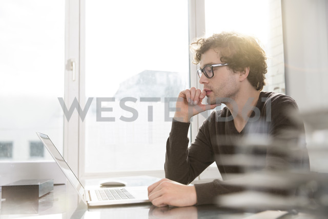 Portrait of young architect using laptop in his office - FKF000421