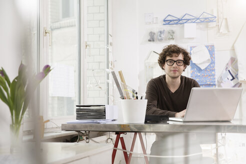 Portrait of young architect sitting at desktop in his office - FKF000461