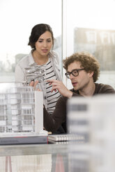 Two young architects with architectural model in office - FKF000429