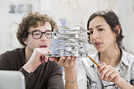 Portrait of two young architects looking at architectural model in office - FKF000431