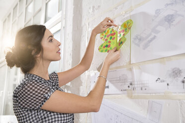 Portrait of young female architect fastening child's painting on pin board - FKF000437
