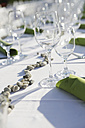 Festive laid table with decoration, green napkins and wine glasses, partial view - JATF000694
