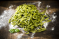 Fresh Tagliatelle Spinaci, leaves of basil and flour on wooden table - MAEF008106
