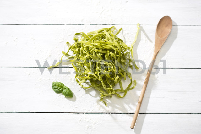 Fresh Tagliatelle Spinaci, leaves of basil, wooden spoon and flour on white wooden table - MAEF008082