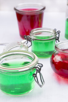 Preserving jars of cherry and woodruff jelly on white ground - LVF000796