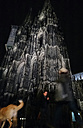 Passers-by and dog at the Cologne Cathedral at Night, Cologne, North Rhine-Westphalia, Germany, - JAT000697