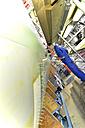 Man working on airplane in a hangar - SCH000046