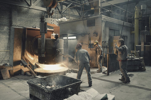 Germany, three men at work in foundry - SCH000100
