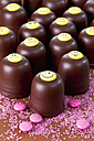 Chocolate marshmallows decorated with different smiley faces, pink sugar and chocolate drops in front - CSF020941