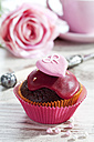 Decorated chocolate muffin in muffin paper on laid table - CSF020947