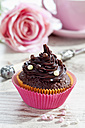 Decorated chocolate muffin in muffin paper on laid table - CSF020956