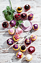 Different decorated muffins in muffin papers, cup, fork and single rose on wooden table, elevated view - CSF020968