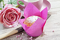 Muffin in pink wrap, rose blossom, cup, fork and sugar beads on wooden table - CSF020977