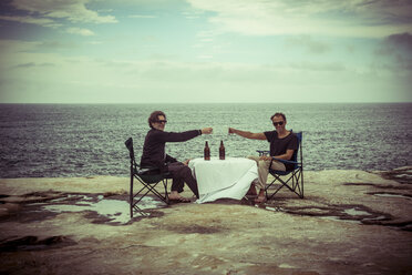 Australia, Sydney, two men sitting with beer at table on cliff - FBF000279