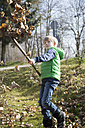 Boy with rake throwing autumn foliage in the air - SARF000329