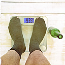 Man in socks on bathroom scales - DRF000554