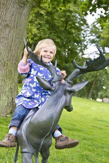 Denmark, Ringkoebing, little girl sitting on deer sculture - JFEF000284