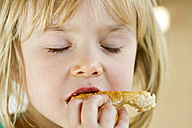 Portrait of little girl eating with closed eyes - JFEF000291