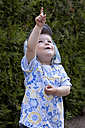 Portrait of little girl pointing at heaven - JFEF000294