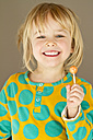 Portrait of happy little girl holding lolly - JFEF000276