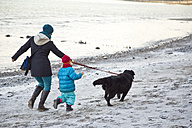 Germany, Schleswig-Holstein, Kiel, mother and daughter walking with labrador along the beach - JFEF000327