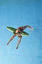 Young man with swim toy floating in water, view from above - PAF000550
