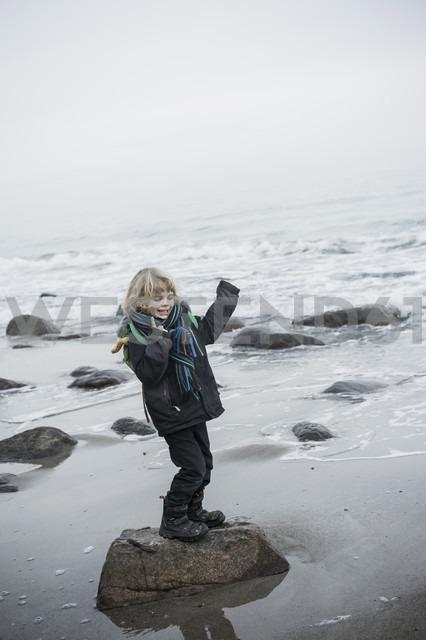 Germany, Mecklenburg-Western Pomerania, Ruegen, happy little boy standing on rock at waterside - MJF000954