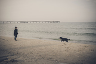 Germany, Mecklenburg-Western Pomerania, Ruegen, little boy and dog on beach in winter - MJ000961