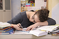 Female pupil with smartphone at her desk - BTF000326