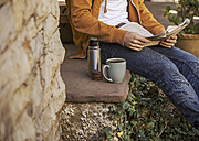 Young man sitting on steps having coffee break, partial view - EBSF000083