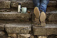 Feet of young man sitting on steps with cup of coffee and thermos flask having a break - EBSF000085